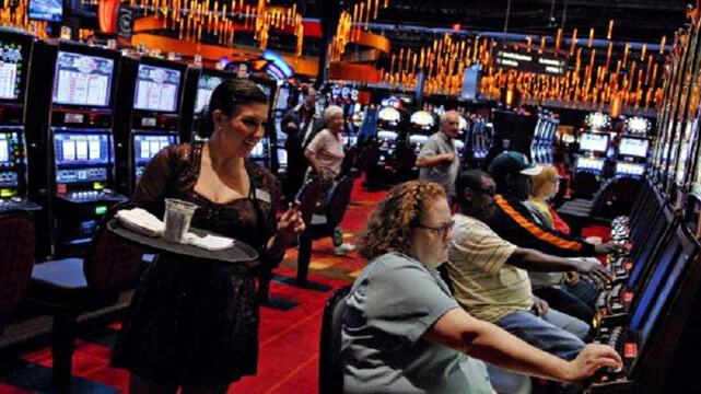 People Playing Slots at the Casino and Getting Drinks